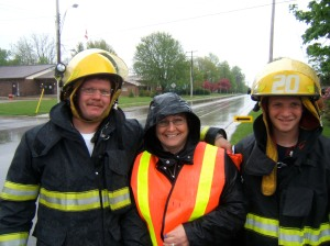 Denise Corneil and two Wardsville Firefighters give out maps to the Shunpikers as they drive through town in the pouring rain.